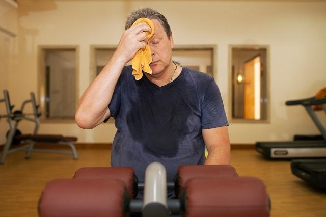 Вытирает пот в фитнес зале